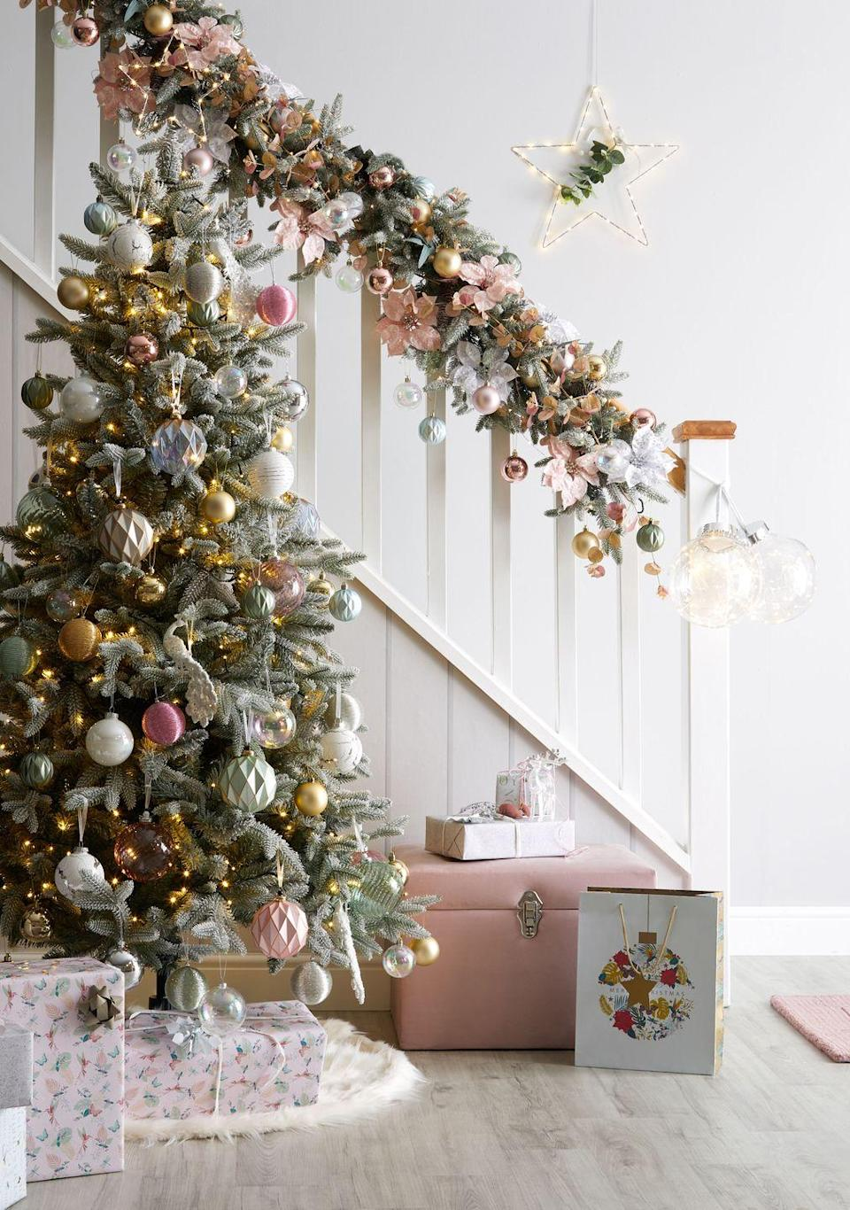 <p>Combine dusky pinks with metallics for Dunelm's Christmas tree trend, Christmas Tropics.</p><p>'A vibrant, tropical twist on Christmas, this glamorous but fun trend blends exotic with traditional,' say Dunelm. 'It mixes fabulous foliage with opulent birds and butterflies.'</p>