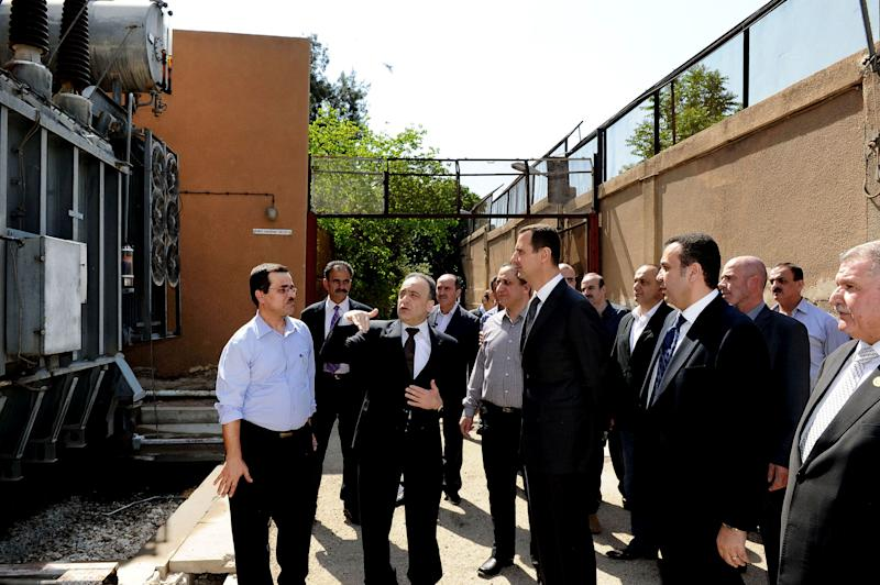 In this photo released by the Syrian official news agency SANA, President Bashar Assad, center, visits the Umayyad Electrical Station on May Day, a day after a powerful bomb hit the capital. in Damascus, Syria, Wednesday, May 1, 2013. (AP Photo/SANA)