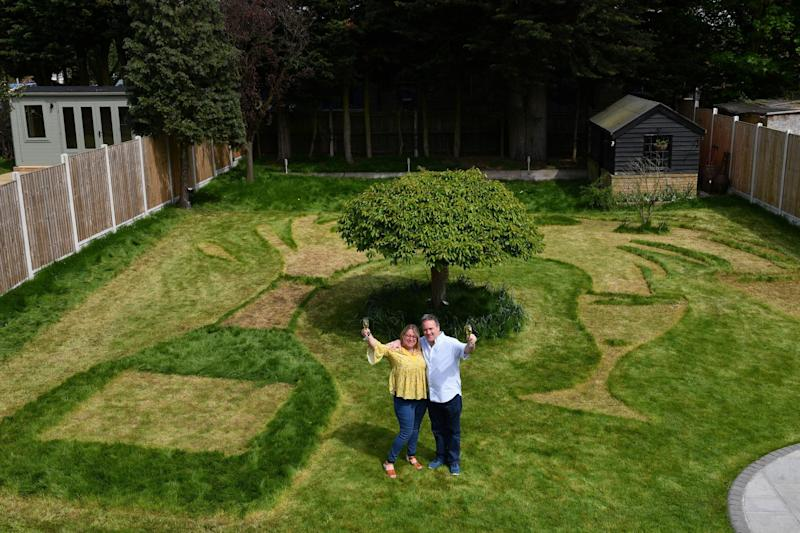 Sue Richards, 51 and 58-year-old Barry Maddox with their new lawn design of a giant champagne bottle and glasses, at their home in Billericay, Essex. (PA Archive/PA Images)