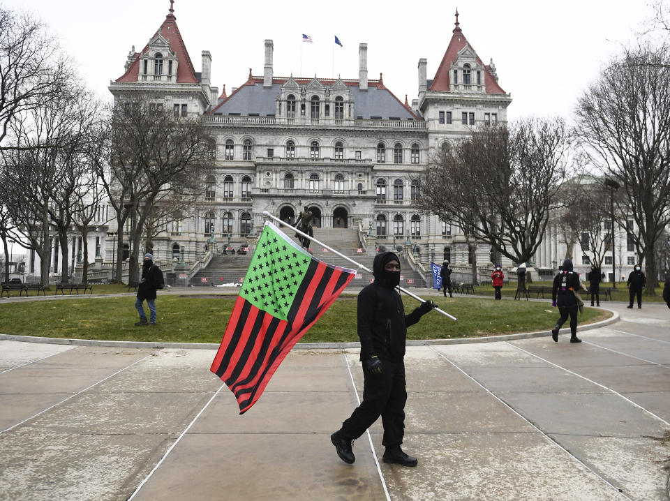 A supporter from Black Liberation walks with a flag while counter protesting a Trump rally ahead of the inauguration of President-elect Joe Biden and Vice President-elect Kamala Harris at the New York state Capitol Sunday, Jan. 17, 2021, in Albany, N.Y. (AP Photo/Hans Pennink)