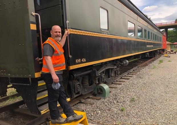 Cory Clark stands in front of the Kamloops Heritage Railway's decommissioned No. 406 railroad car. The car is being turned into a classroom to allow the Heritage Railway to host field trips starting in September 2021. (Brendan Coulter/CBC - image credit)