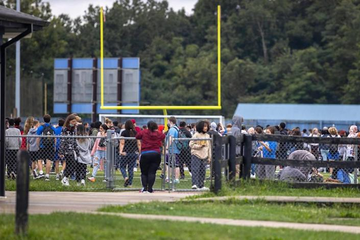 Students from Henry Clay High School stand on the football field after the school was evacuated because of a bomb threat on Tuesday, Sept. 21, 2021.