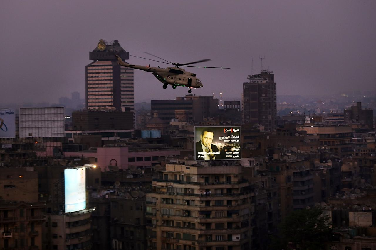 CAIRO, EGYPT - JULY 03: An Egyptian military helicopter flies over Tahrir Square after a broadcast by the head of the Egyptian military confirming that they will temporarily be taking over from the country's first democratically elected president Mohammed Morsi on July 3, 2013 in Cairo, Egypt. As unrest spreads throughout the country, at least 23 people were killed in Cairo on Tuesday and over 200 others were injured. It has been reported that the military has taken over the state television. (Photo by Spencer Platt/Getty Images)