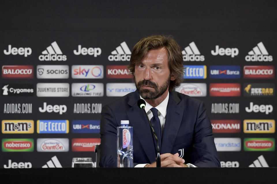 Andrea Pirlo sits in front of a microphone at a podium.