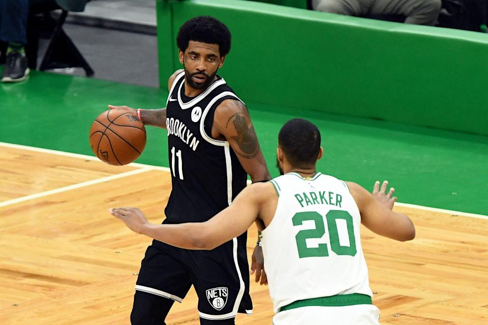 Brooklyn Nets guard Kyrie Irving (11) dribbles the ball in front of Boston Celtics forward Jabari Parker (20) during the second half of Game 4.