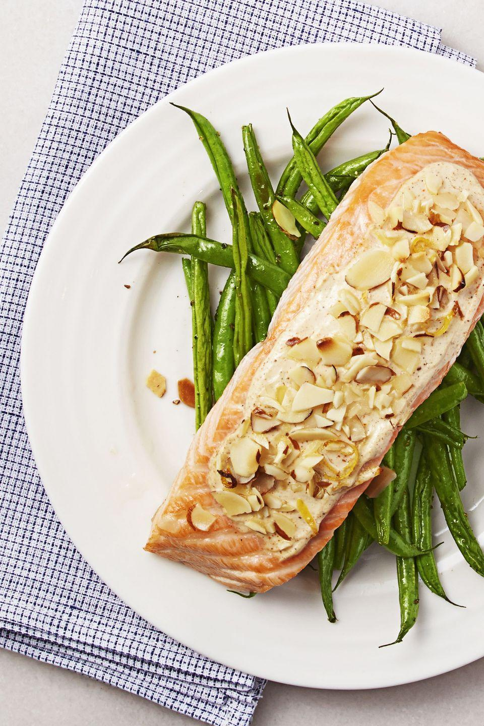 """<p>This delicately plated salmon may look like it requires a ton of prep work, but the reality is that you simply rub it with spices — and let the oven do the rest! A side of green beans can go on the bottom rack.</p><p><em><a href=""""https://www.goodhousekeeping.com/food-products/a32681/almond-crusted-creole-salmon/"""" rel=""""nofollow noopener"""" target=""""_blank"""" data-ylk=""""slk:Get the recipe for Almond-Crusted Creole Salmon »"""" class=""""link rapid-noclick-resp"""">Get the recipe for Almond-Crusted Creole Salmon »</a></em></p>"""
