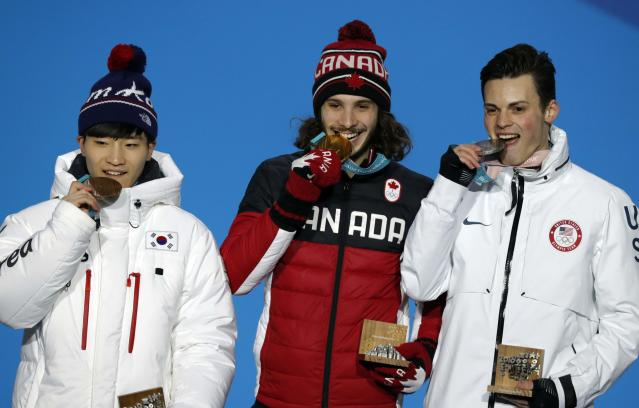 Medals Ceremony - Short Track Speed Skating Events - Pyeongchang 2018 Winter Olympics - Men's 1000m - Medals Plaza - Pyeongchang, South Korea - February 18, 2018 - Gold medalist Samuel Girard of Canada, silver medalist John-Henry Krueger of the U.S. and bronze medallist Seo Yi-ra of South Korea on the podium. REUTERS/Eric Gaillard