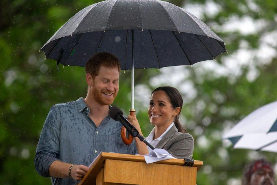 <p>Meghan Markle lets Prince Harry stand under her umbrella as he carries on with a speech after it started to rain in Dubbo, Australia. </p>