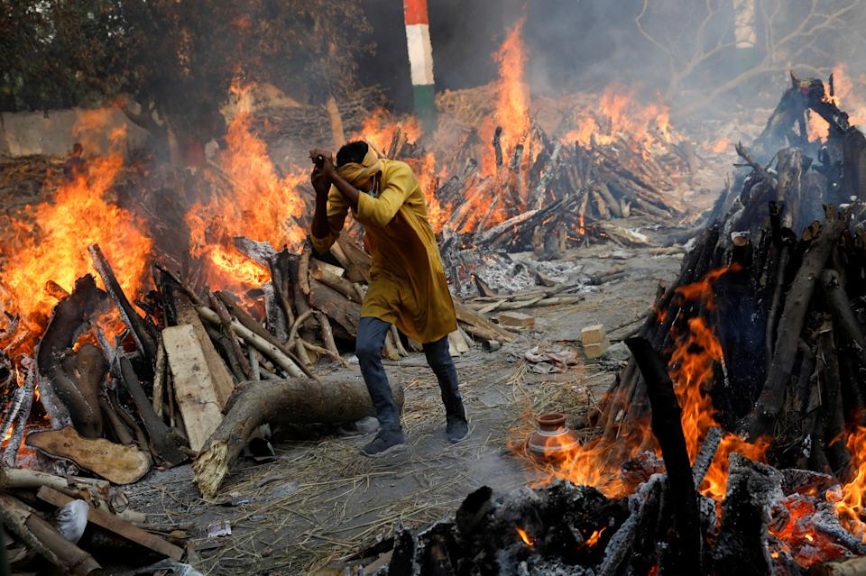 A man runs past the burning funeral pyres of those who died from the coronavirus disease (COVID-19), during a mass cremation, at a crematorium in New Delhi, India April 26, 2021. REUTERS/Adnan Abidi     TPX IMAGES OF THE DAY