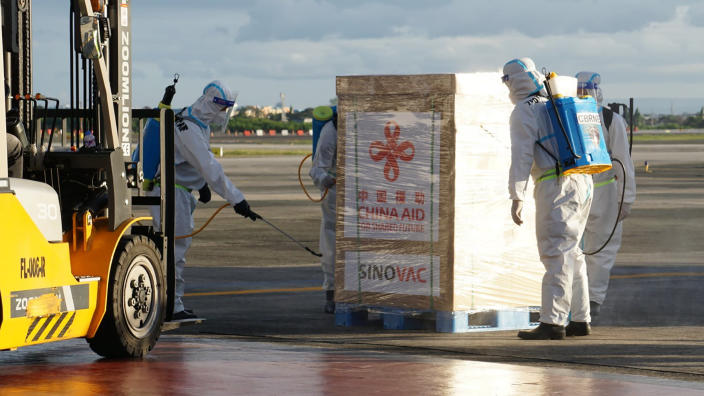 In this photo provided by the Presidential Communications Operations Office-Office of the Global Media Public Affairs, the first batch of Sinovac vaccine from China is sanitized as it arrives at the Villamor Air Base in Manila, Philippines on Sunday Feb. 28, 2021. The Philippines is due to receive its first batch of COVID-19 vaccine Sunday, among the last in Southeast Asia to secure the critical doses despite having the second-highest number of coronavirus infections and deaths in the hard-hit region. (PCOO-OGMPA via AP)