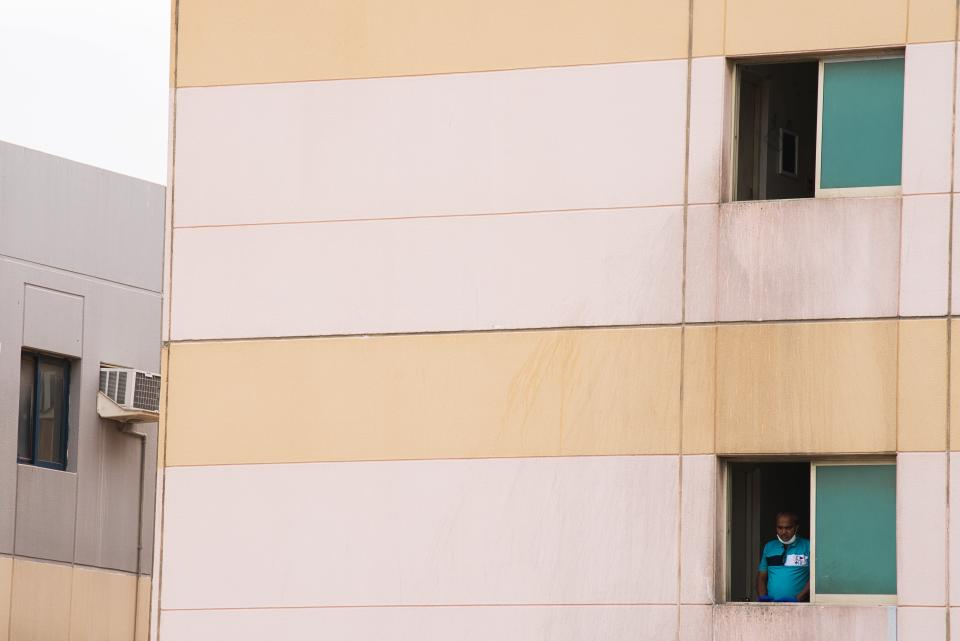 In this Thursday, April 16, 2020 photo, a laborer looks out the window of his living quarters in the Al Quoz neighborhood of Dubai, United Arab Emirates. Migrant workers in oil-rich Gulf Arab states have long been a lifeline for their families back home but they now find themselves trapped by the coronavirus pandemic. They are losing jobs, running out of money and desperate to return home as COVID-19, the illness caused by the virus, stalks their labor camps. (AP Photo/Jon Gambrell)
