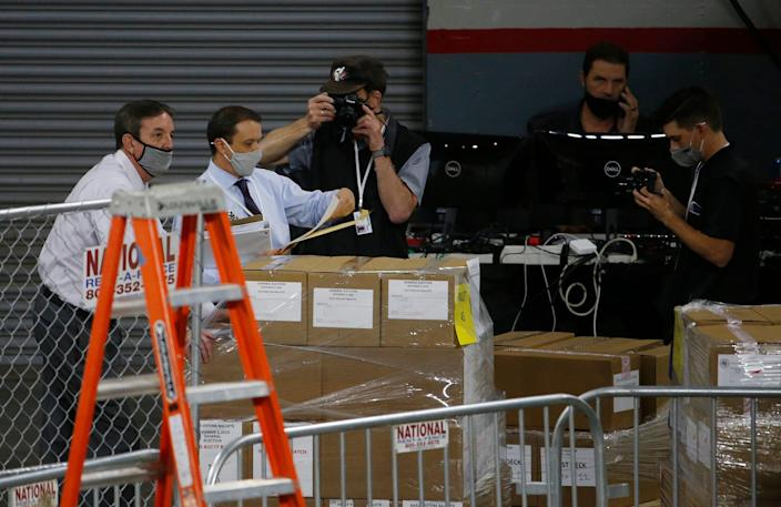 Former Arizona Secretary of State Ken Bennett (left) takes custody of a pallet of ballots before an audit of the 2.1 million election ballots at Veterans Memorial Coliseum in Phoenix on April 22, 2021.
