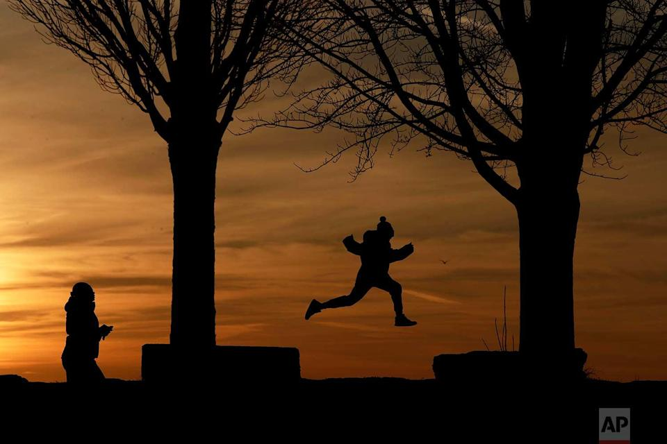 <p>A child leaps between rock platforms as the sun sets behind Lake Erie at the Erie Basin Marina in Buffalo, N.Y. (AP Photo/Julio Cortez) </p>
