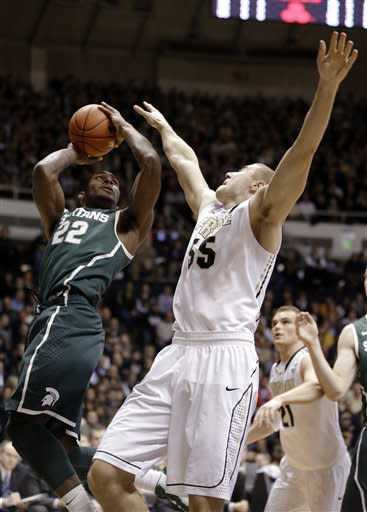 Michigan State guard Branden Dawson, left, shoots over Sandi Marcius in the first half of an NCAA college basketball game in West Lafayette, Ind., Saturday, Feb. 9, 2013. (AP Photo/Michael Conroy)