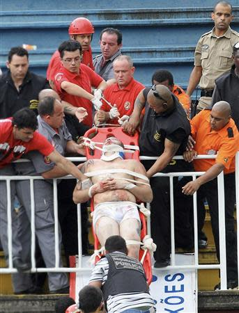 Paramedics use a stretcher to carry an injured Atletico Paranaense fan after clashes between fans of Vasco da Gama and Atletico Paranaense during their Brazilian championship match in Joinville in Santa Catarina state December 8, 2013. REUTERS/Carlos Moraes