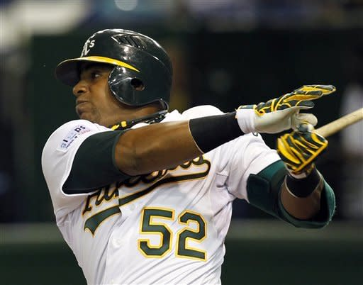 Oakland Athletics centerfielder Yoenis Cespedes hits a two-run shot against Seattle Mariners starter Jason Vargas in the seventh inning of their American League MLB baseball game at Tokyo Dome in Tokyo Thursday, March 29, 2012. (AP Photo/Koji Sasahara)
