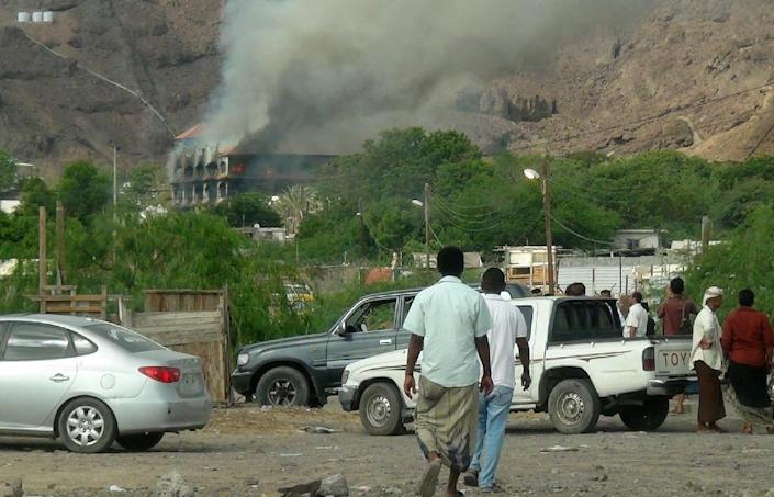 Yemenis gather as flames and smoke rise from Sheikh bin Farid palace, used as a base by the Saudi-led coalition forces, after it was attacked on October 6, 2015 on the outskirts of Aden (AFP Photo/Saleh al-Obeidi)