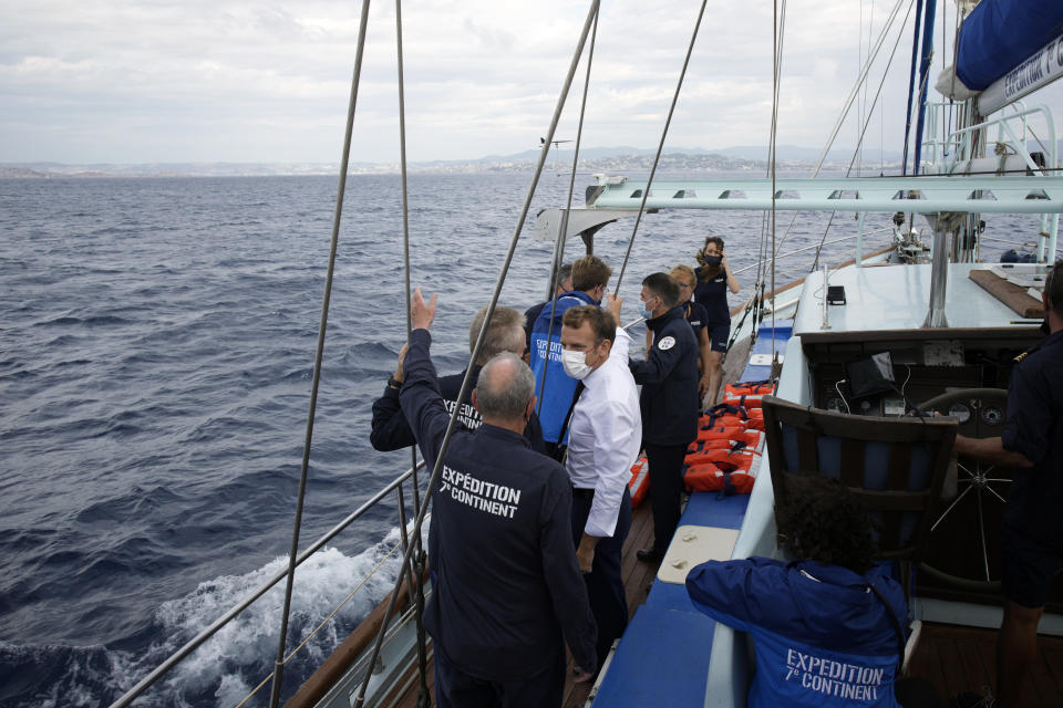 French President Emmanuel Macron talks with the crew of the 7th Continent expedition sailing ship as they go admire the Calanques National Park, a marine reserve known for its azure blue waters overhung by high white cliffs, near Marseille, southern France, Friday Sept. 3, 2021. Macron is expected to urge the world to better protect biodiversity as key to fight climate change and support human welfare at a global summit starting Friday in southern France. (AP Photo/Daniel Cole, pool)