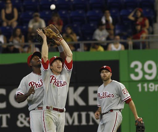 Philadelphia Phillies right fielder Nate Schierholtz (22) watches as left fielder John Mayberry (back) and second baseman Chase Utley (26) almost collide as Utley catches a fly ball hit by Miami Marlins batter Austin Kearns during the eighth inning of a MLB baseball game in Miami, Sunday, Sept. 30, 2012. The Phillies won 4-1. (AP Photo/J Pat Carter)