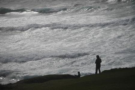 People look out at rough sea from Slea Head during Storm Ali in Coumeenoole, Ireland, September 19, 2018. REUTERS/Clodagh Kilcoyne