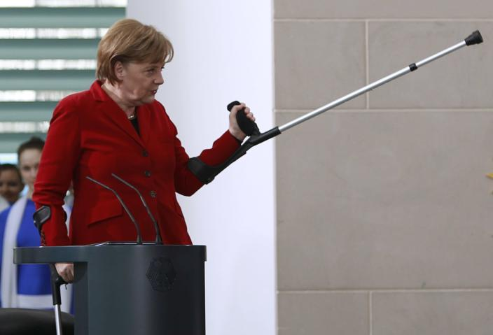 File photo of German Chancellor Angela Merkel gesturing with her crutch during a reception of people working in honorary offices during a reception at the Chancellery in Berlin, April 5, 2011. German Chancellor Angela Merkel has fractured her pelvis in a cross-country skiing accident and is walking with the help of crutches, forcing her to call off some foreign visits and official appointments, her spokesman said January 6, 2014. Merkel fell while skiing over the Christmas vacation. What she first thought was heavy bruising turned out to be a partial fracture, meaning she must take it easy for three weeks and work from home where possible, said her spokesman Steffen Seibert. REUTERS/Thomas Peter/Files (GERMANY - Tags: POLITICS SOCIETY)
