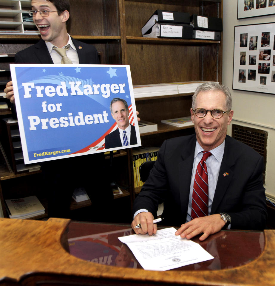 Kevin Miniter, state campaign coordinator smiles at left, as Republican presidential candidate, Fred Karger  fills out his form at Secretary of State's office in Concord, N.H., Monday, Oct. 17, 2011, to be on the ballot for the New Hampshire presidential primary.  (AP Photo/Jim Cole)