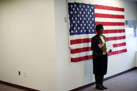 A new American citizen poses for a photograph during a naturalization ceremony in Newark, New Jersey, March 1, 2017. REUTERS/Mike Segar