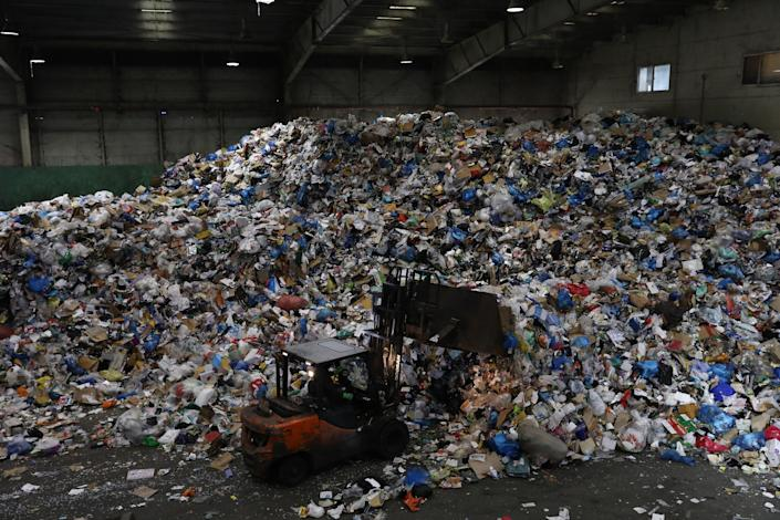 <p> A forklift truck moves household waste at a facility in Seoul, South Korea  </p> (Getty)