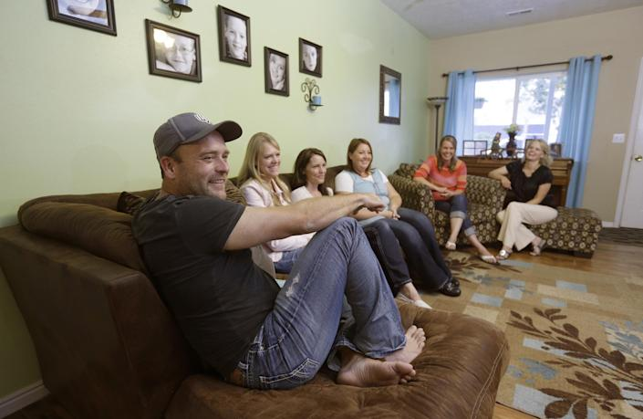 FILE - In this Sept. 11, 2013, file photo, Brady Williams talks while his wives, from left to right, Robyn, Paulie, Rosemary, Nonie, and Rhonda, look on during an interview at their home in a polygamous community outside Salt Lake City. The newest Utah polygamous family featured in a reality TV show says sharing their story with a wide audience has been liberating. Brady Williams and his five wives were a bit apprehensive ahead of the airing of a pilot episode in September, but they said this week an interview with The Associated Press that it felt liberating to be open about who they are and what they believe. (AP Photo/Rick Bowmer, File)