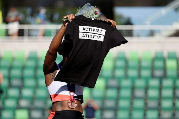 PHOTO: Gwendolyn Berry holds up a shirt that reads 'Activist Athlete' as she celebrates finishing third in the Women's Hammer Throw final at the 2020 U.S. Olympic Track & Field Team Trials at Hayward Field on June 26, 2021, in Eugene, Ore. (Patrick Smith/Getty Images)