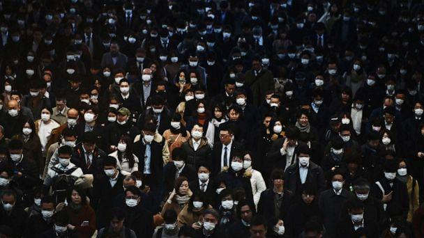 PHOTO: Mask-clad commuters make their way to work during morning rush hour at the Shinagawa train station, in Tokyo on Feb. 28, 2020. \ (Charly Triballeau/AFP via Getty Images)