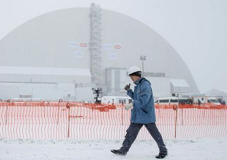 A worker is seen in front of a New Safe Confinement (NSC) structure over the old sarcophagus covering the damaged fourth reactor at the Chernobyl nuclear power plant, Ukraine, November 29, 2016. REUTERS/Gleb Garanich