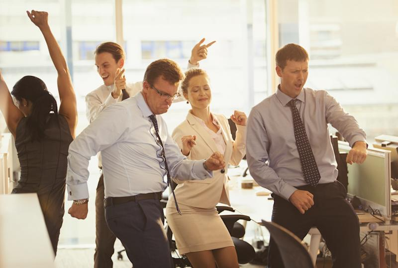 Enthusiastic business people celebrating and dancing in office
