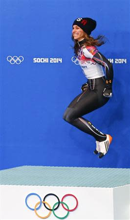 Noelle Pikus-Pace of the U.S. jumps on the podium as she celebrates second place in the women's skeleton event at the 2014 Sochi Winter Olympics, at the Sanki Sliding Center in Rosa Khutor February 14, 2014. REUTERS/Arnd Wiegmann