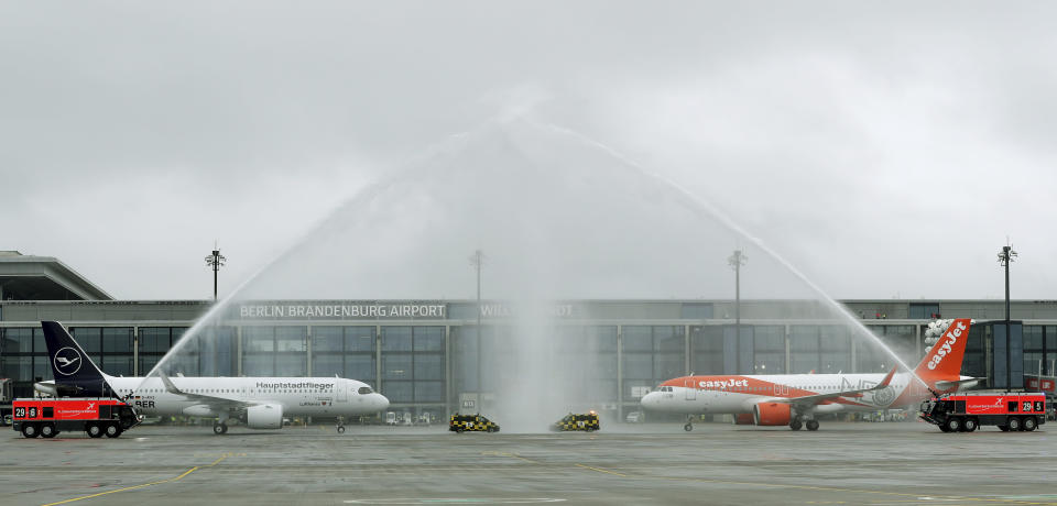 The airport fire brigade sprays water onto a 'Lufthansa', left, and 'easyJet' ariplane that are parked in front of Terminal 1 after their arrival at the new Berlin-Brandenburg-Airport 'Willy Brandt' in Berlin, Germany, Saturday, Oct. 31, 2020. Berlin's new airport opens after years of delays and cost overruns. (AP Photo/Michael Sohn)