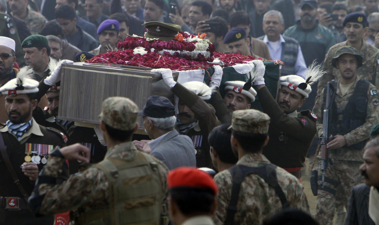 People attend the funeral of a Pakistani soldier in Lahore, Pakistan, Wednesday, Dec. 13, 2017. Pakistan's army says militants opened fire on an army vehicle on patrol in the country's mountainous northwestern region near the Afghan border, killing two soldiers. (AP Photo/K.M. Chaudary)