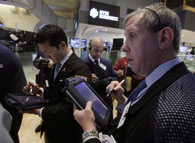 In this May 30, 2012 photo, Richard Cohen, right, works with fellow traders on the floor of the New York Stock Exchange. U.S. futures augured a lower opening on Wall Street Friday June 1, 2012.   (AP Photo/Richard Drew)