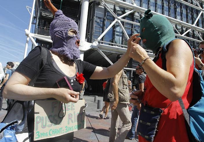 Demonstrators adjust their masks during a demonstration in support of the Russian punk group Pussy Riot during a protest in Paris Friday Aug. 17, 2012. Three members of Pussy Riot were jailed in March and charged with hooliganism motivated by religious hatred after their punk performance against President Putin in Moscow's main cathedral. They are awaiting the verdict later Friday, Aug. 17, 2012. Banner reads: 3 minutes of song 3 years of jails.(AP Photo/Jacques Brinon)