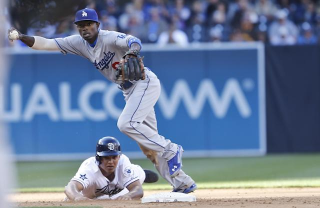 Los Angeles Dodgers second baseman Dee Gordon is unable to make a relay to first to complete a double play after the hard slide by San Diego Padres' Will Venable in the fifth inning of baseball game Tuesday, April 1, 2014, in San Diego. (AP Photo/Lenny Ignelzi)