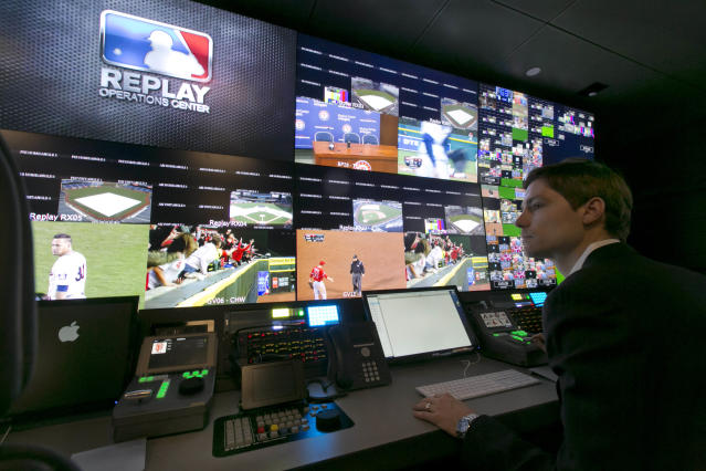 Chris Marinak sits in front of a bank of television screens during a preview of Major League Baseball's Replay Operations Center, in New York, Wednesday, March 26, 2014. Less than a week before most teams open, MLB is working on the unveiling of its new instant replay system, which it hopes will vastly reduce incorrect calls by umpires. (AP Photo/Richard Drew)