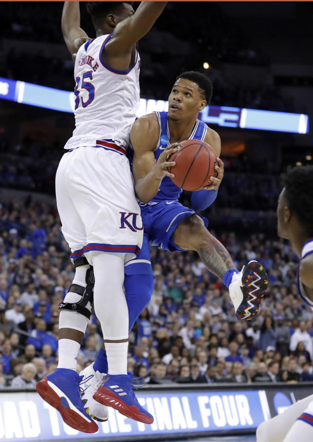 Duke's Trevon Duval, right, looks to the basket as Kansas' Udoka Azubuike defends during the first half of a regional final game in the NCAA men's college basketball tournament Sunday, March 25, 2018, in Omaha, Neb. (AP Photo/Charlie Neibergall)