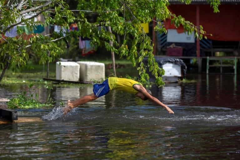 A boy enjoys the river in the Brazilian village of Sao Raimundo do Jaraua -- learning to swim in the Amazon river basin also means learning to avoid piranhas and caimans