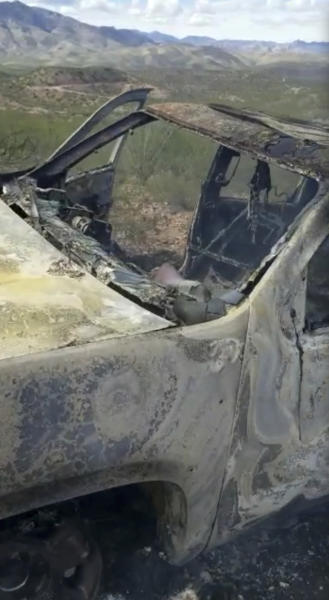 This frame from Nov. 4, 2019, video by Kenny Miller and posted on the Twitter account of Alex LeBaron shows a burned-out vehicle that was being used by some members of the LeBaron family as they were driving in a convoy near the Sonora-Chihuahua border in Mexico. Mexican authorities say drug cartel gunmen ambushed multiple vehicles, including this one, slaughtering several women and children. (Kenny Miller/Courtesy of Alex LeBaron via AP)