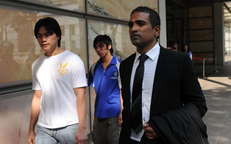 Yong Yun Leong (L) and Yong Yun Chung, brothers of convicted Malaysian drug trafficker Yong Vui Kong, leave the High Court with lawyer M. Ravi, in Singapore, on April 4, 2011