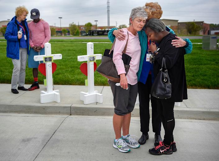 Members of the Billy Graham Rescue Response Team pray with Lancelot DeSilva, second left, Susan Cox, third from right, and Valerie Aaron, right, at a memorial outside the Antioch Waffle House for the four people killed by a gunman on April 25, 2018.