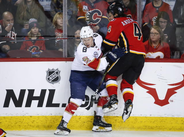 Florida Panthers' Jayce Hawryluk, left, checks Calgary Flames' Rasmus Andersson, of Sweden, during an NHL hockey game in Calgary, Alberta, Friday, Jan. 11, 2019. (Jeff McIntosh/The Canadian Press via AP)