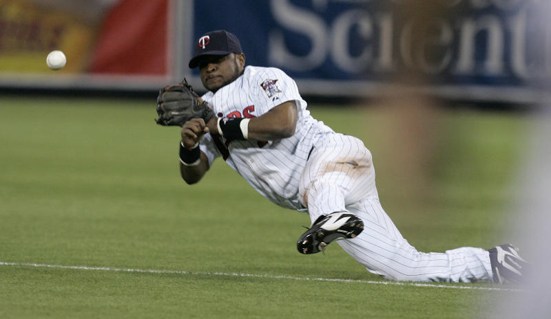 FILE - In this June 12, 2007 file photo, Minnesota Twins second baseman Luis Castillo makes an off-balance throw to first base in an unsuccessful attempt to throw out Atlanta Braves' Kelly Johnson on an infield single during the second inning of a baseball game in Minneapolis. Authorities in the Dominican Republic arrested on Tuesday, Aug. 20, 2019, former MLB pitcher Octavio Dotel and are searching for ex-infielder Luis Castillo for their alleged links to a drug-trafficking and money-laundering ring in the Caribbean and United States. (AP Photo/Ann Heisenfelt, File)