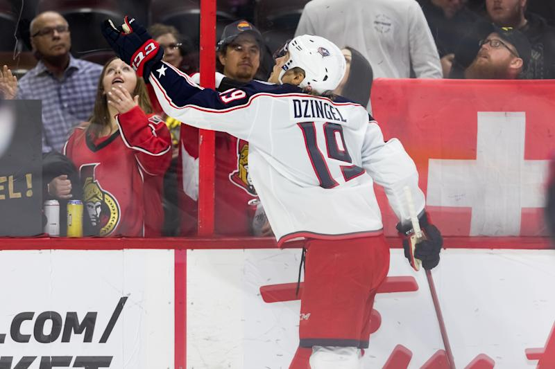 OTTAWA, ON - APRIL 06: Columbus Blue Jackets Left Wing Ryan Dzingel (19) tosses a puck over the glass to fans during warm-up before National Hockey League action between the Columbus Blue Jackets and Ottawa Senators on April 6, 2019, at Canadian Tire Centre in Ottawa, ON, Canada. (Photo by Richard A. Whittaker/Icon Sportswire via Getty Images)