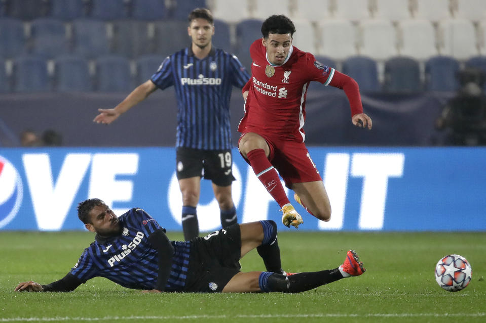 Atalanta's Jose Luis Palomino, on the ground, fights for the ball with Liverpool's Trent Alexander-Arnold during the Champions League, group D soccer match between Atalanta and Liverpool, at the Gewiss Stadium in Bergamo, Italy, Tuesday, Nov. 3, 2020. (AP Photo/Luca Bruno)