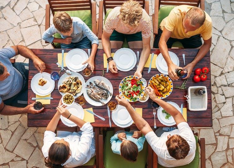 A family sitting around a dinner table eating.